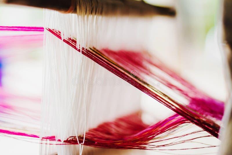 关闭泰国丝绸编织在一台传统织布机 库存照片