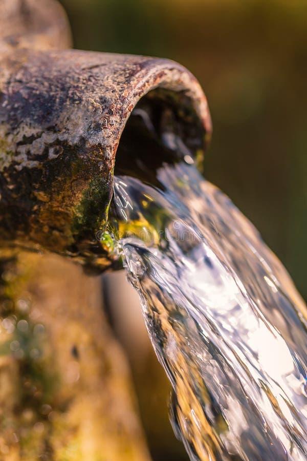 关闭流动从一个开放回合生锈的年迈的和破旧的管子的清楚的水 免版税图库摄影