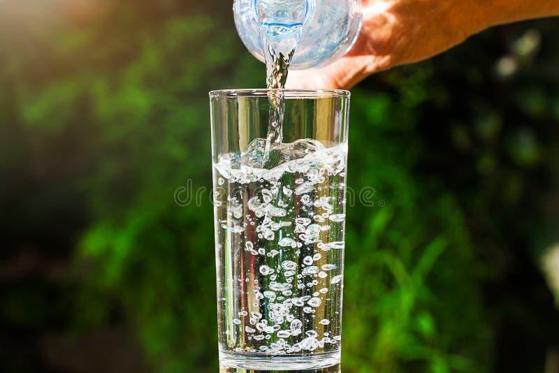关闭流动从饮用水瓶的水入在被弄脏的绿色庭院背景的玻璃 库存图片