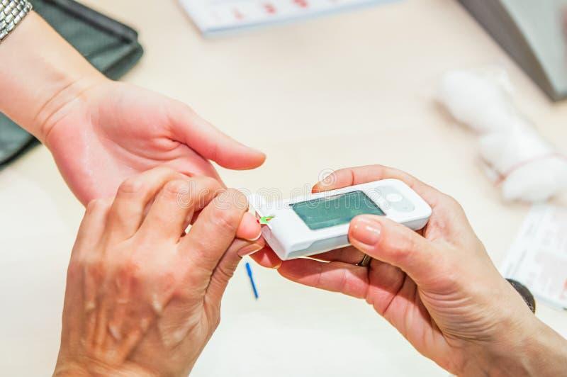 关闭流动糖尿病测试的过程糖水平的 正常血糖水平 医生采取测试医疗proces的血液 免版税库存照片