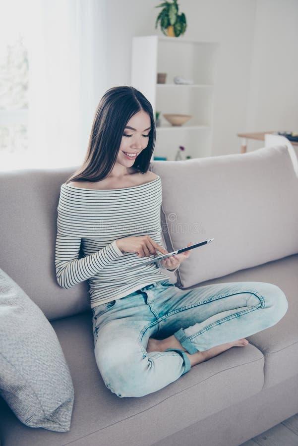 关闭浏览在她的片剂的年轻快乐的中国夫人播种的照片,坐米黄长沙发户内在家,佩带casu 免版税库存照片