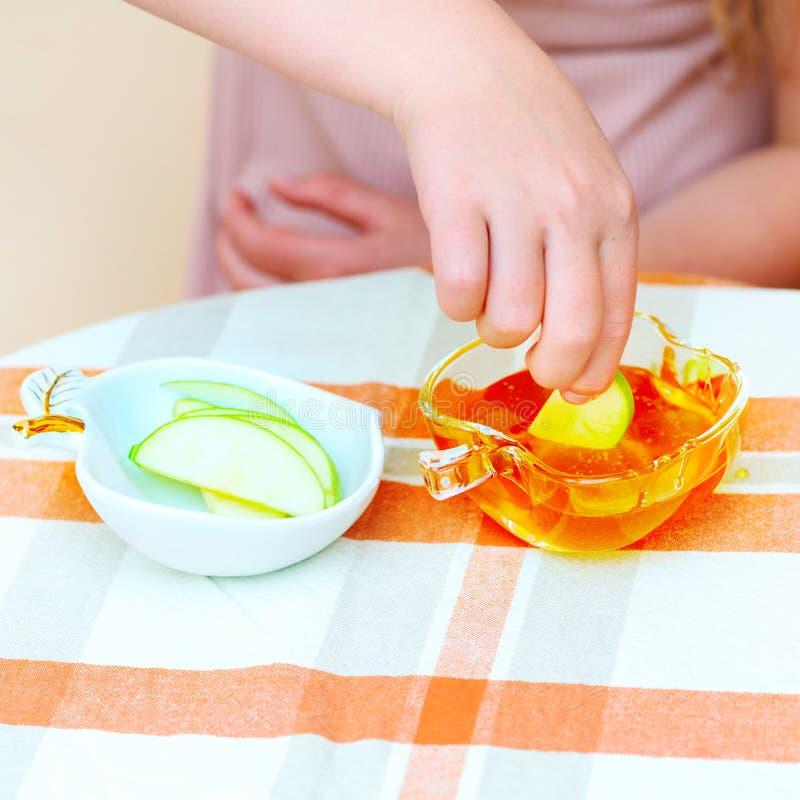 关闭浸洗苹果切片的手犹太孩子入在犹太新年的蜂蜜 免版税库存照片