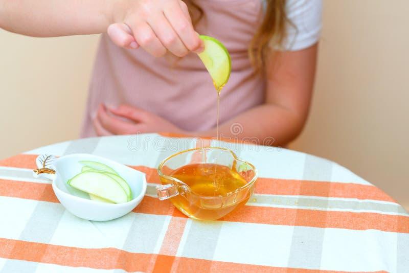 关闭浸洗苹果切片的手犹太孩子入在Rosh Hashana的蜂蜜 免版税库存照片