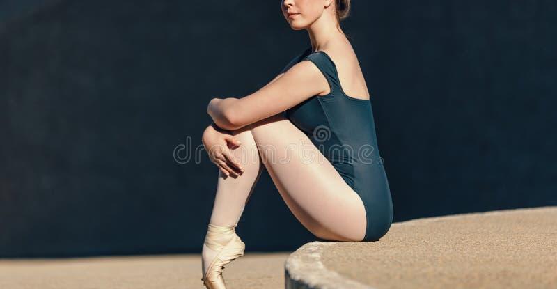 关闭温文地坐女性的跳芭蕾舞者,当restin时 免版税库存图片