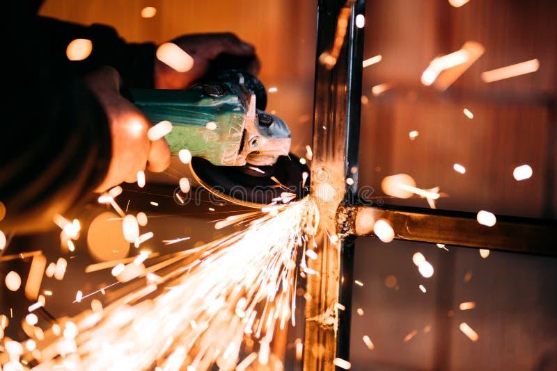 关闭火花,使用角度研磨机的产业工人细节和切开钢 库存图片