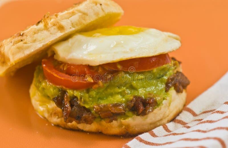 关闭烟肉、果酱、鲕梨和蛋松饼三明治 免版税库存照片