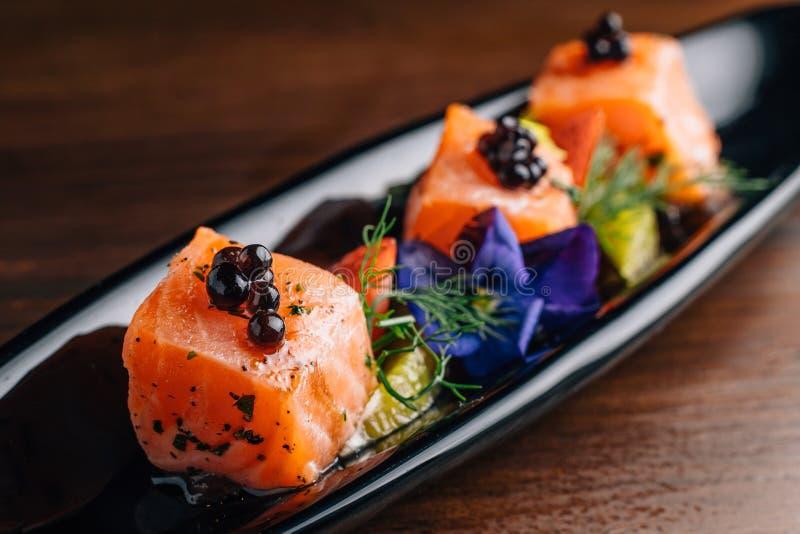 关闭烤了半生半熟三文鱼立方体冠上用鱼子酱和服务用草莓和桔子在黑色的盘子 免版税库存图片
