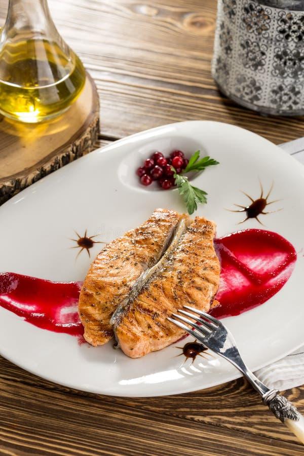 关闭烤鲑鱼排用蔓越桔和红色调味汁在木桌上 免版税图库摄影