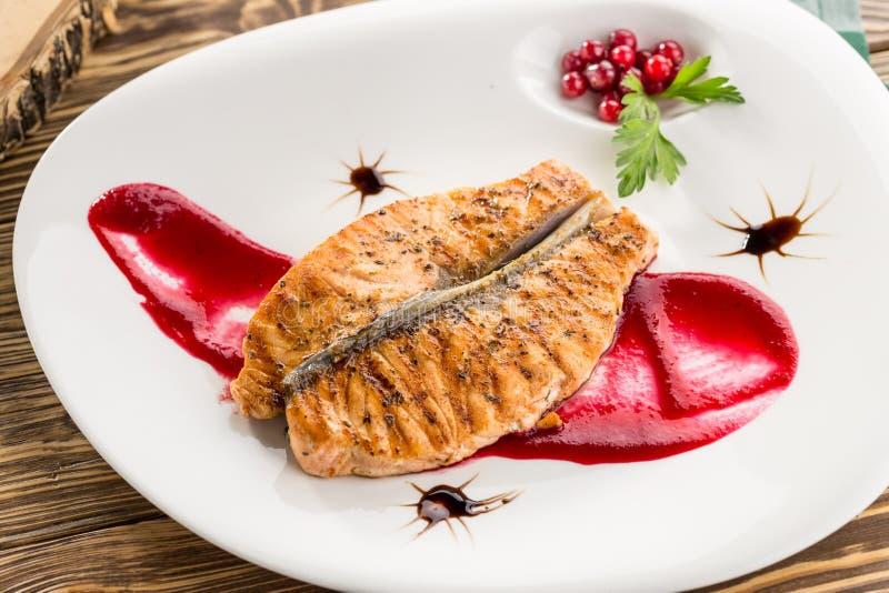 关闭烤鲑鱼排用蔓越桔和红色调味汁在木桌上 库存图片