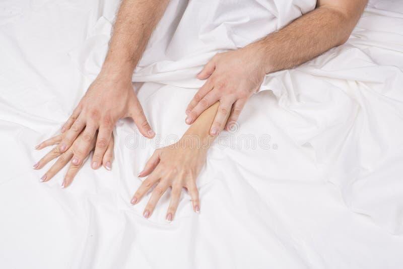 关闭热情的夫妇停滞手在做强烈的爱期间在卧室,恋人享受在白色板料的热的性 免版税图库摄影
