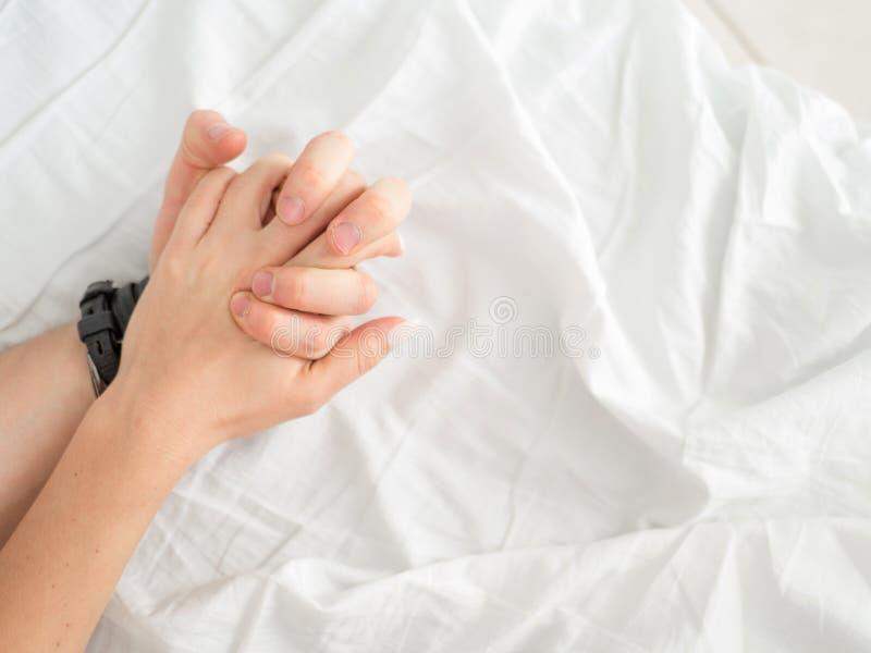 关闭热情的夫妇停滞手在做强烈的爱期间在卧室,恋人享受在白色板料的热的性 免版税库存图片