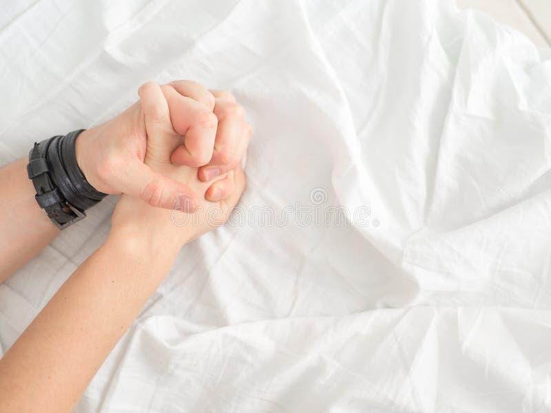 关闭热情的夫妇停滞手在做强烈的爱期间在卧室,恋人享受在白色板料的热的性 免版税库存照片