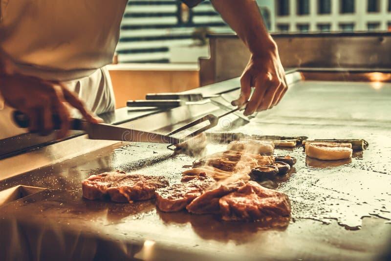 关闭烹调牛排和菜在热的平底锅的手厨师 免版税库存图片