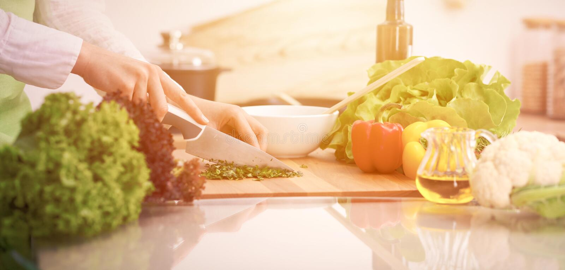 关闭烹调菜沙拉的人的手在玻璃桌上的厨房里与反射 健康膳食,和 库存图片