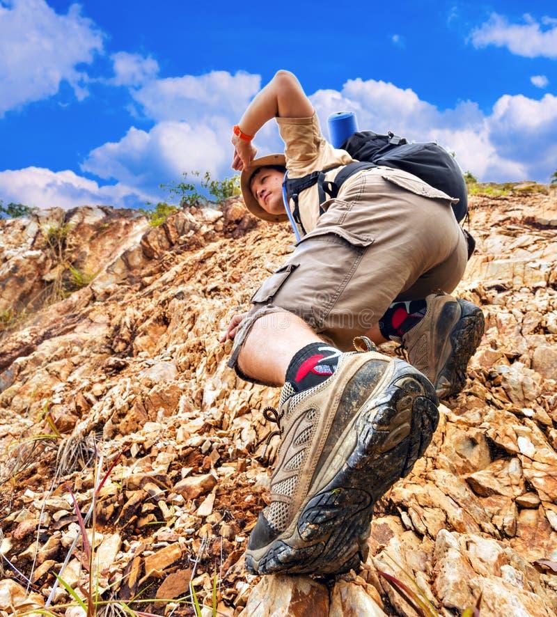 关闭爬上红色岩石的一个人 库存图片