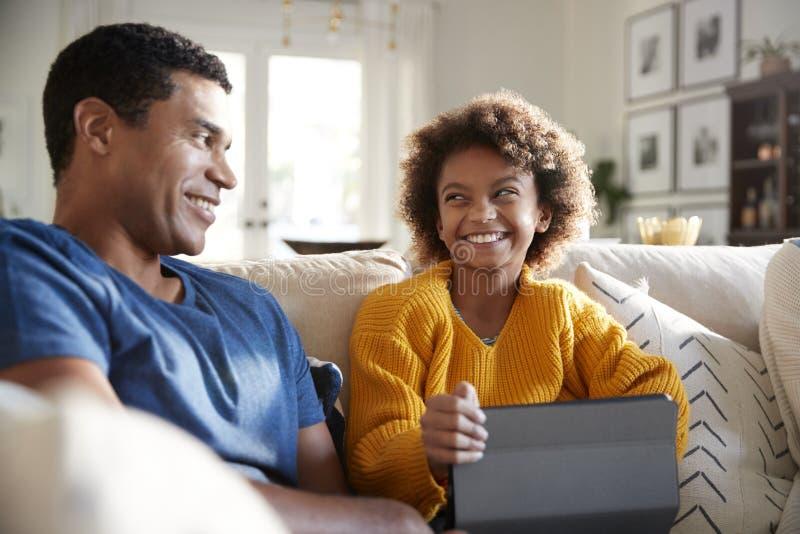 关闭父亲和女儿坐沙发在客厅微笑对彼此的,选择聚焦 免版税库存图片