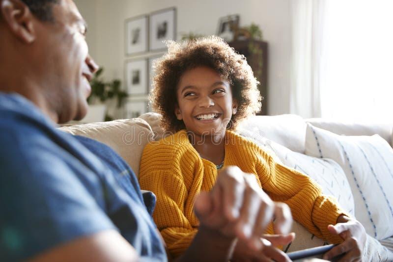 关闭父亲和女儿坐沙发在笑的客厅看彼此和,选择聚焦 免版税库存图片