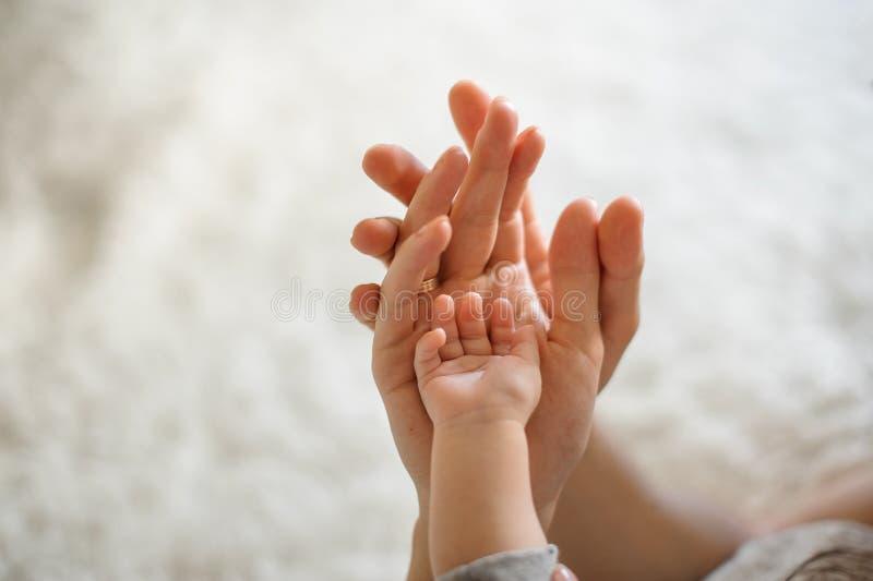 关闭父母和婴孩加入在轻的背景的手 免版税库存图片