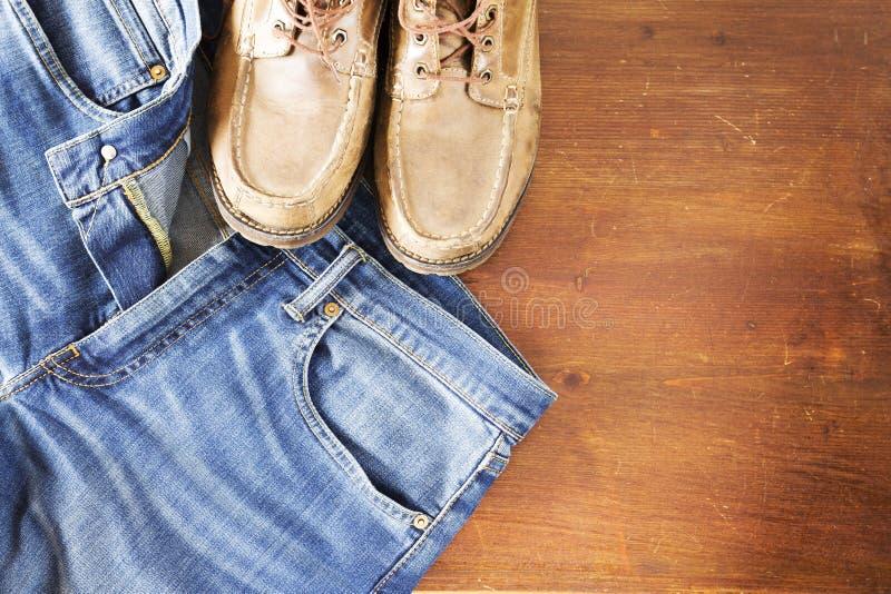 关闭牛仔裤裤子和人在木背景的` s鞋子 库存图片