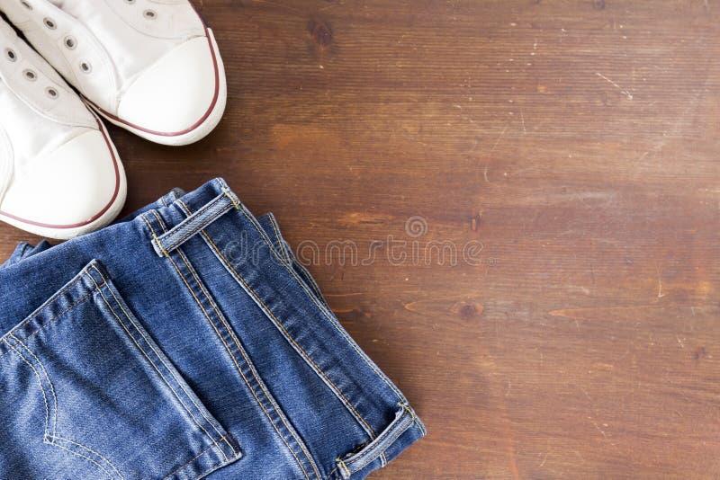 关闭牛仔裤裤子和运动鞋在木背景 库存图片