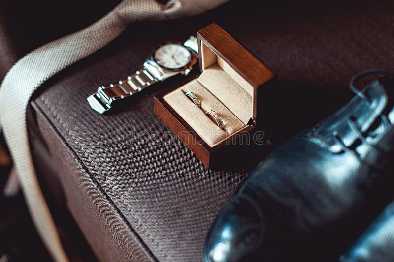 关闭现代新郎辅助部件 在一块棕色木箱、领带,皮鞋和手表的婚戒 免版税库存图片