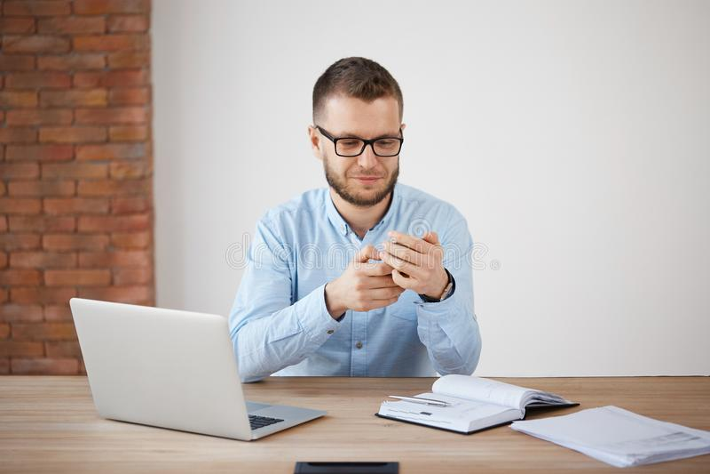 关闭玻璃和衬衣的成熟不剃须的人在工作,聊天与妻子由智能手机在午餐期间 经理 免版税库存照片