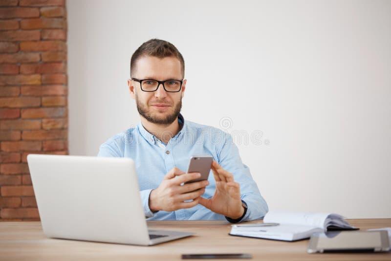 关闭玻璃和衬衣的成熟不剃须的男性经理在办公室,工作坐便携式计算机,聊天  免版税库存照片