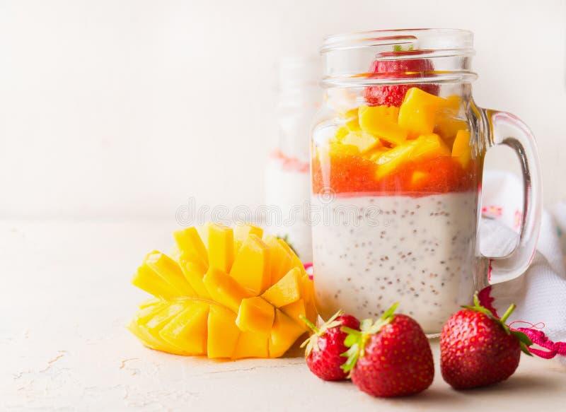 关闭玻璃瓶子用chia种子酸奶布丁、芒果和草莓在白色桌上 r 健康素食主义者早餐 图库摄影