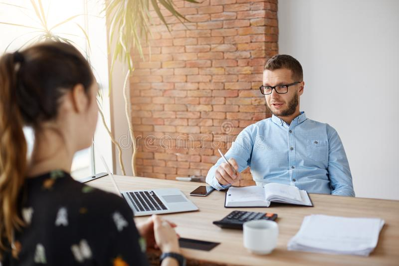 关闭玻璃的成熟有胡子的公司董事在有深色头发的女孩的办公室在他前面坐工作 免版税库存图片