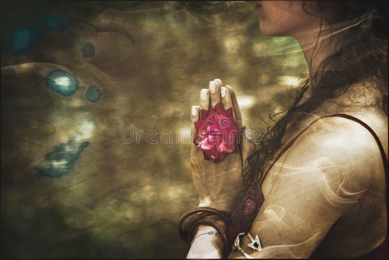 关闭瑜伽在namaste姿态的妇女手与玫瑰色花 免版税库存图片