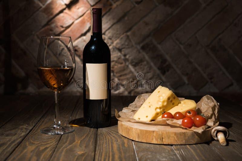 关闭瓶和杯看法酒用乳酪和爽快蕃茄在烘烤纸在木 免版税图库摄影