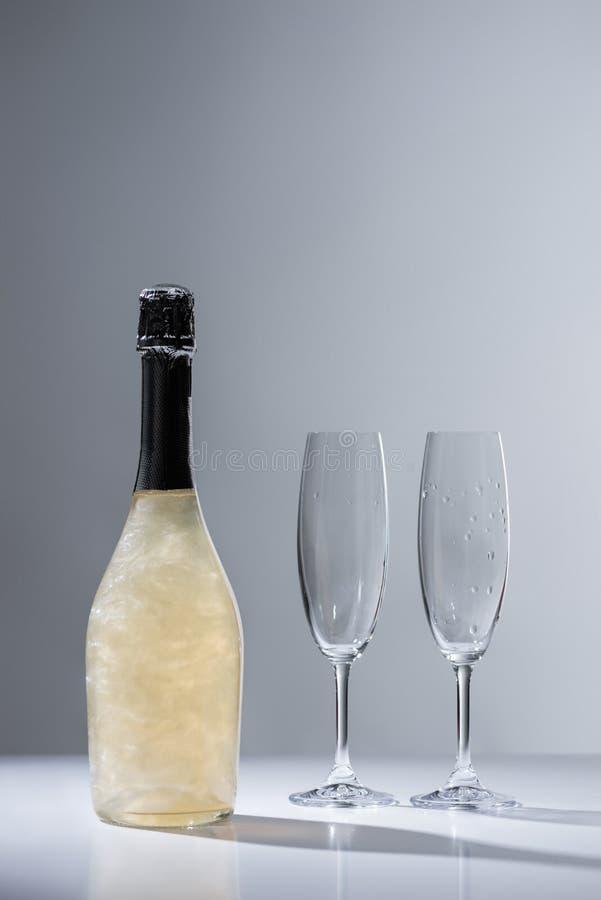 关闭瓶看法香槟和空的玻璃 库存照片