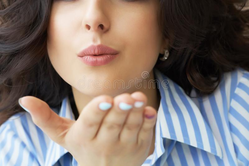 关闭甜可爱的深色的与棕榈噘嘴嘴唇的妇女吹的空气亲吻画象在照相机 库存图片