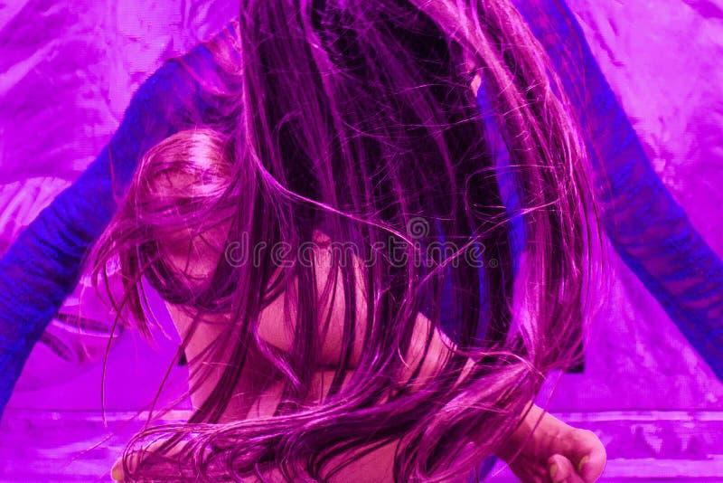 关闭甩她的在聚酯薄膜帐篷的一副霓虹蓝色上面和蓝色太阳镜的一美女头发在紫外照明设备下 免版税库存图片