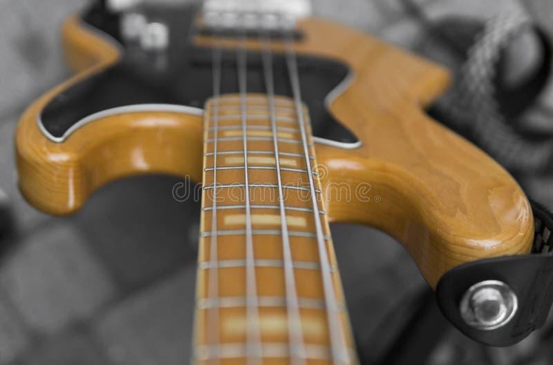 关闭电子低音吉他指板 与音量控制器的木低音 免版税库存图片