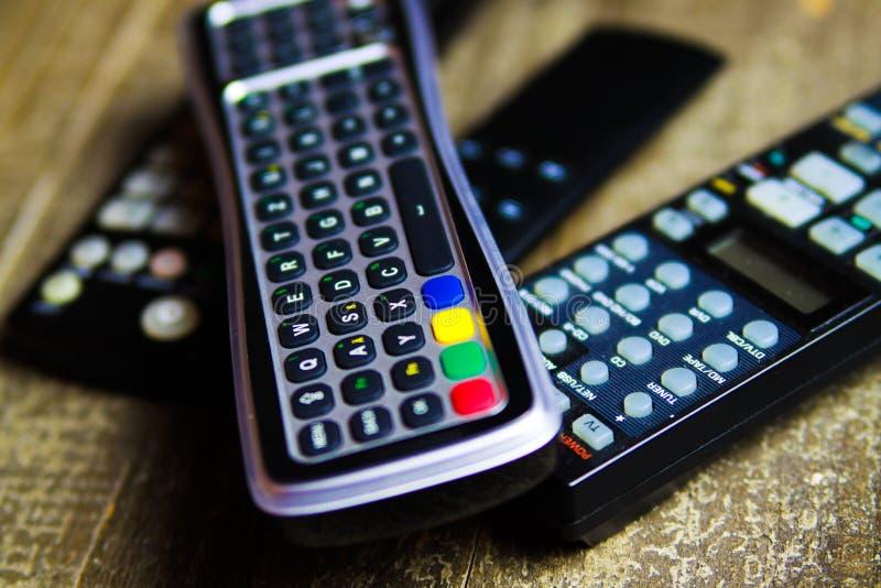 关闭电视、录影和立体声音乐系统的遥控在木桌上 免版税库存照片