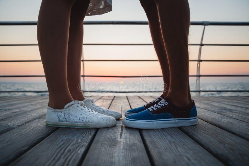 关闭男人和妇女行家在运动鞋的夫妇脚在海滩在日出天空在木甲板夏时,在黄色蓝色e 免版税库存图片