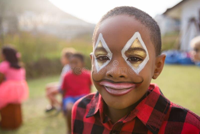 关闭男孩画象有面孔油漆的 库存照片