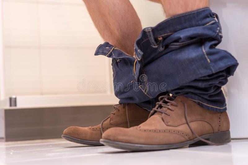 关闭男性佩带的牛仔裤和鞋子看法坐toi 免版税图库摄影