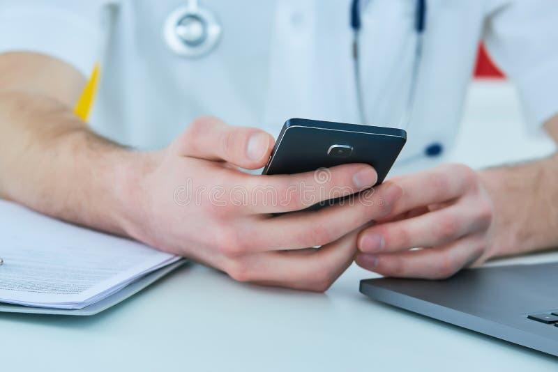关闭男性医生或使用流动巧妙的电话的医科学生研究便携式计算机在医院 免版税库存图片