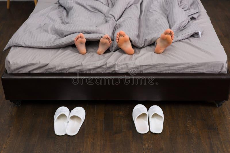 关闭男性和女性脚在灰色毯子下,在两pa附近 库存图片