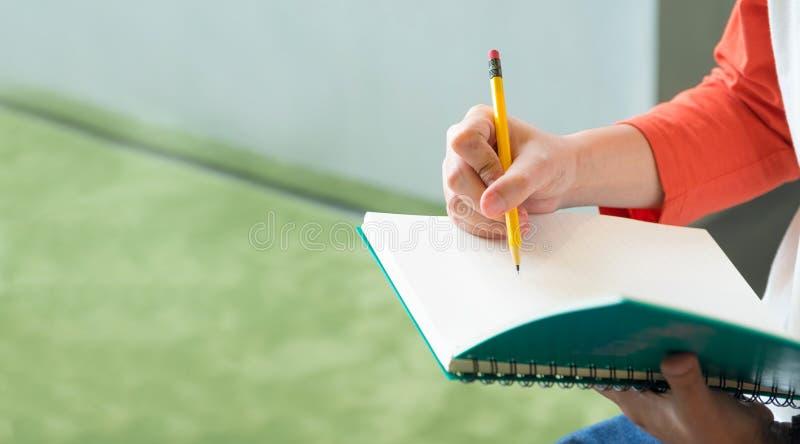 关闭男性少年文字的手与铅笔的在笔记本a 免版税图库摄影