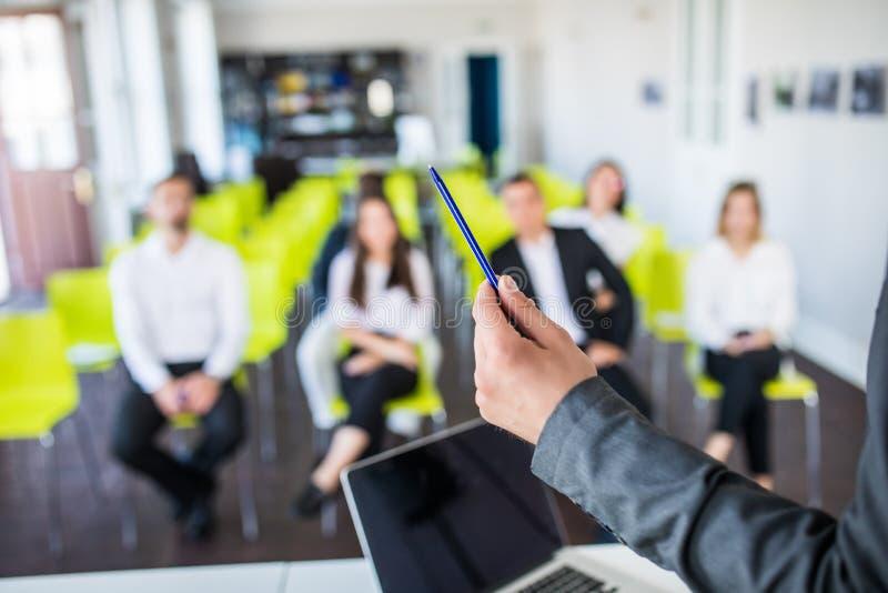 关闭男性辅导者或教练举行文书工作,给flipchart介绍,谈话与雇员 商人有 图库摄影