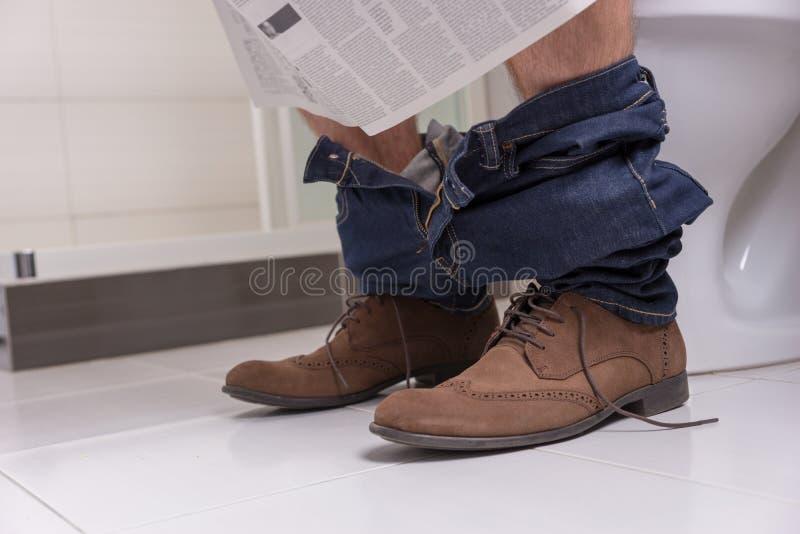 关闭男性读书报纸看法,当坐toi时 免版税库存照片