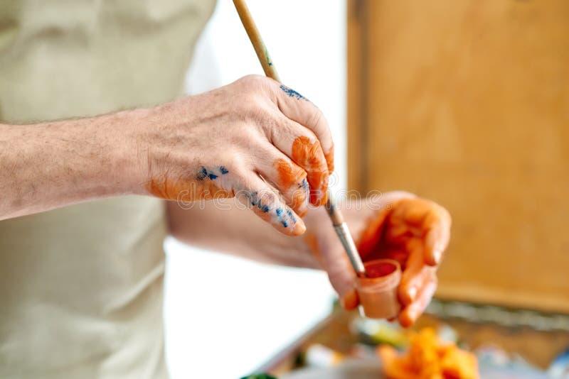 关闭画家的手与油或丙烯酸酯一起使用在明亮的演播室 免版税图库摄影
