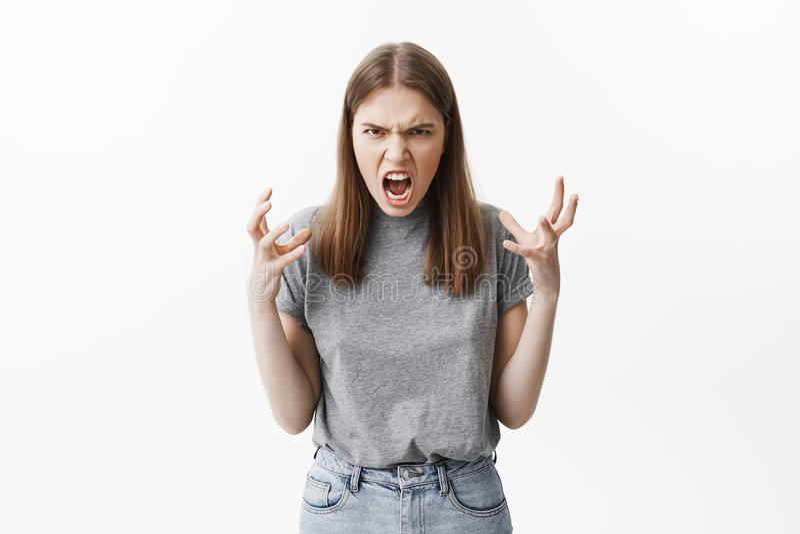 关闭疯狂的美丽的白种人学生女孩画象有棕色头发的在看在照相机的便衣以恼怒 免版税库存图片