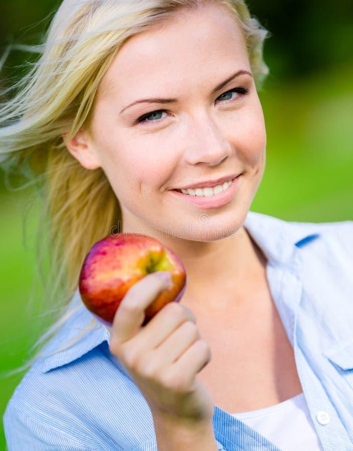 关闭白肤金发的妇女用苹果 免版税图库摄影