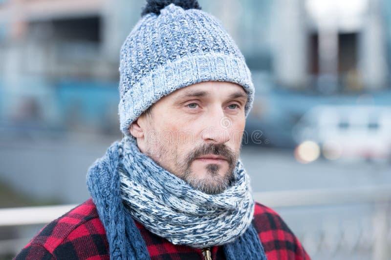 关闭白色男性在城市 白人画象在街道上的 冬天帽子的有胡子的人有球和红色夹克的 免版税图库摄影