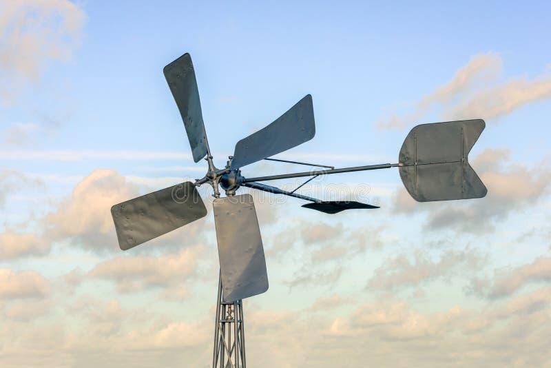 从关闭的被恢复的老金属风车反对多云天空 免版税库存照片