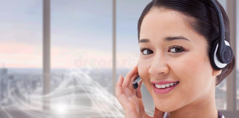 关闭的综合图象摆在与耳机的一名微笑的操作员 图库摄影
